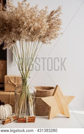Neutral Beige Decor Colors. Glass Vase Bottle With A Bouquet Of Dry Ears, Crocheted Jute Baskets, Pu