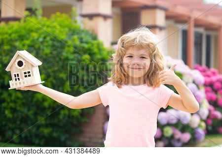 Happy Child Holding Toy House In Hands Against New Home. Concept Of Housing For Kids.