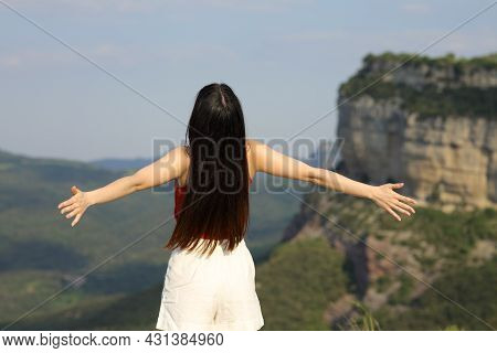 Back View Portrait Of A Woman Outstretching Arms Contemplating In The Mountain