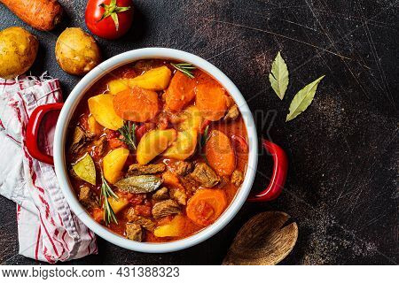 Slow Cooked Beef Stew With Potatoes And Carrots In Tomato Sauce In Red Pot, Dark Background, Top Vie