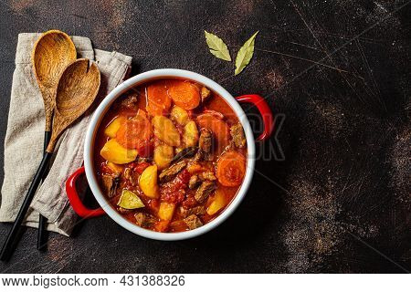 Slow Cooked Beef Stew With Potatoes And Carrots In Tomato Sauce In Red Pot, Dark Background. Slow Co