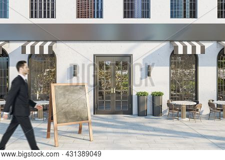 Young Businessman In Suit Walking Past Creative Concrete Cafe Exterior With Terrace Furniture And Em