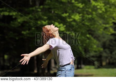 Happy Woman Screaming To The Air Outstretching Arms In A Forest