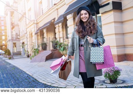 Young Brunette Curly Woman Is Holding Shopping Bags, Standing Against Old City Street. Fashionable F