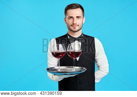 Elegant Male Waiter With Glasses Of Wine Over Blue Background