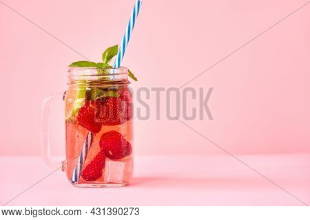Strawberry Homemade Lemonade In A Mason Jar With Copy Space On Pink Background.