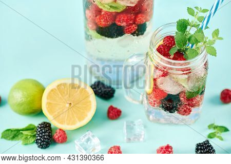 Fresh Berries Cocktail In Glass Jar. Fresh Summer Cocktail With Mix Of Berries, Lemon And Mint On Bl