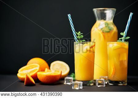Delicious Orange Juice With Ice, Mint And Fresh Fruits On Black Table Background With Copy Space