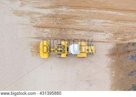 Aerial View Of The Working Yellow Earth Mover Grader Flattens The Surface.