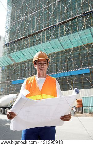 Contractor In Hard Hat Rolling Out Construction Plan Of Building