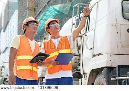 Contractors In Bright Orange Vests, Hard Hats And Goggle Standing At Construction Site And Discussin