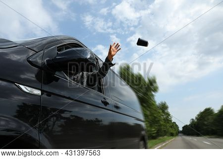 Driver Throwing Away Paper Coffee Cup From Car Window, Low Angle View. Garbage On Road