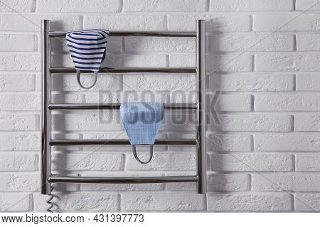 Modern Heated Towel Rail With Cloth Face Masks On White Brick Wall
