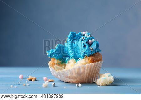 Failed Cupcake On Blue Wooden Table, Closeup. Troubles Happen