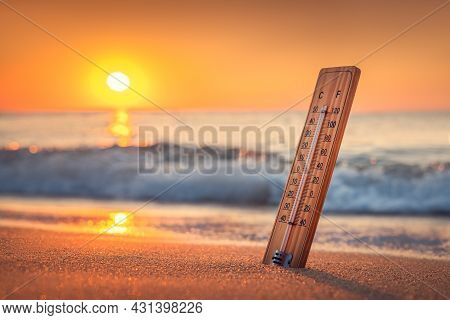 Thermometer And Sunrise Over The Beach. The Heat. Hot Summer Day.