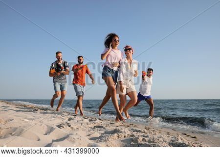 Group Of Friends With Water Guns Having Fun On Beach