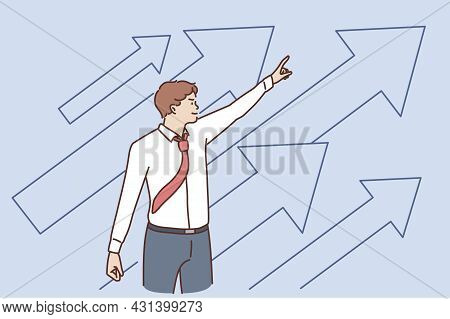 Business Development And Success Concept. Young Positive Businessman Standing Pointing Up With Arrow