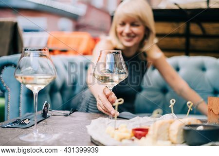 Happy And Laughing Adult Mature Woman Sitting In Bar Outdoors With Wine Glasses And Blurry Restauran