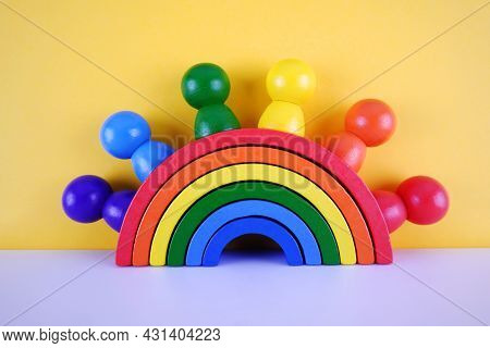 Wooden Imitation Of People Over A Colorful Waldorf Rainbow On A Yellow Background.montessori Concept