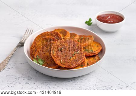 Lentil Fritters With Plum Sauce, Tkemali, Greens In A White Plate On A Light Blue Textured Backgroun