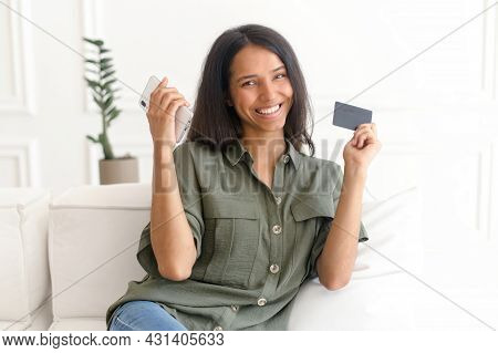 Cheerful Young Indian Woman Making An Order Online, Holds A Smartphone And A Debit Card, Pays For Th