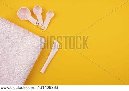 Pink Set For A Face Mask On An Orange Background. Plastic Bowl, Spoons And Towel For Spa Hair Care T