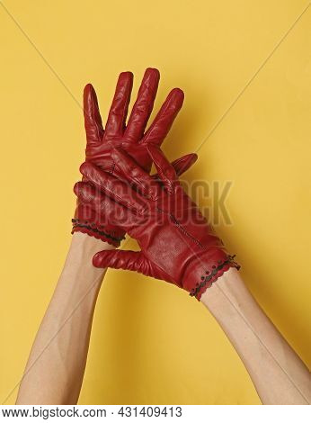 Skinny Female Hands Wearing Leather Red Gloves On Yellow Background
