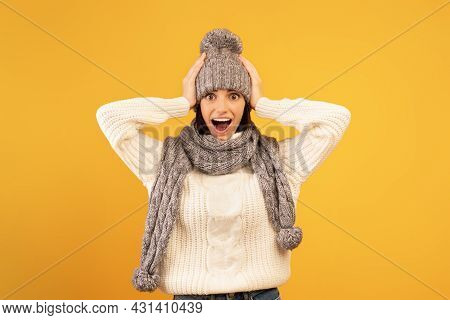 Wow, Such A Nice Deal. Overjoyed Lady In Knitted Hat And Scarf Looking At Camera With Open Mouth, Ye