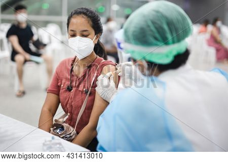 Female In Protective Mask Receiving Injection Of Coronavirus Vaccine.