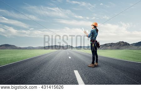 Young Woman In Safety Helmet Standing On Asphalt Highway With Blueprint. Back View Architect In Work