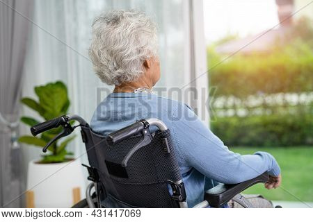 An Elderly Woman Sitting On Wheelchair Looking Out The Window For Waiting Someone. Sadly, Melancholy