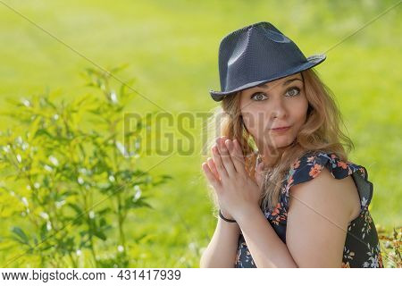 Young Girl In A Hat Is Making A Grimace At The Camera In Summer Day. Horizontally.