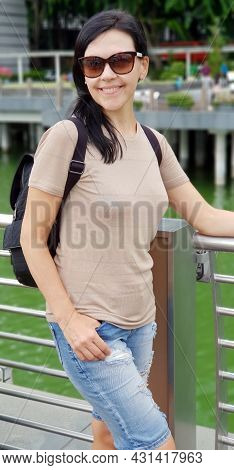 Smiling Young Woman Tourist With Backpack In Singapore
