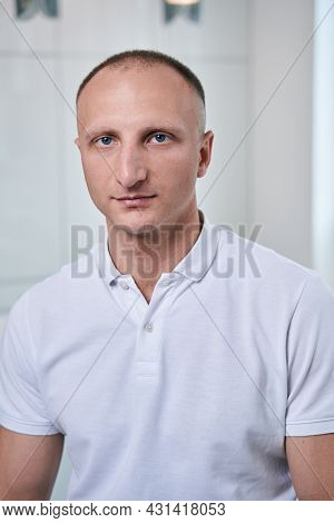 Seriously Osteopath In Uniform Looking And Posing At The Photo Camera In His Medical Office