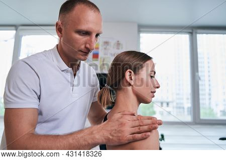 Well Built Caucasian Male Acupressure Specialist Examining Woman Back Pain In Medical Office