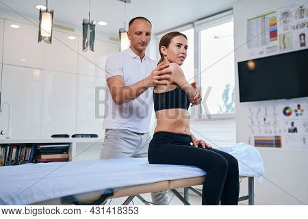 Handsome Acupressure Specialist Working With Female Patient In Medical Office