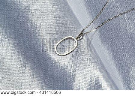 Elegant Oval Pendant On Neck Chain Lying On Gray Background Under Sunshine. Jewelry Fashion Photogra