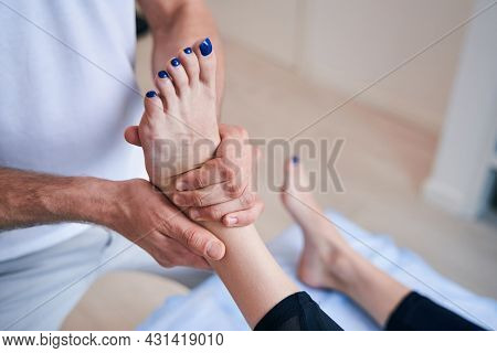 Unrecognized Male Acupressure Specialist Working With Legs Of Woman In Medical Office
