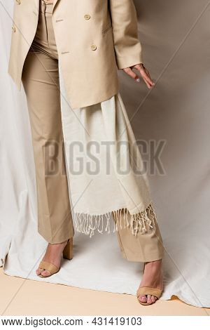 Partial View Of Woman In Beige Suit And Heels Standing On Drapery