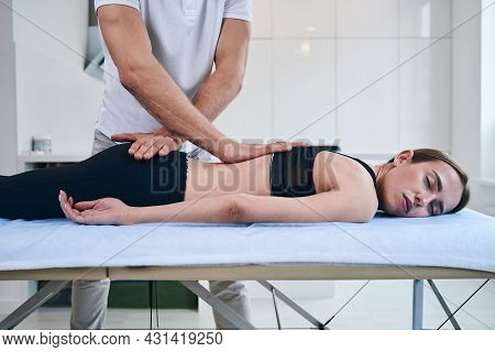Unrecognized Man Osteopath Stretching Back Of Beautiful Lady In Rehabilitation Clinic