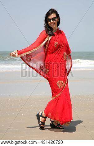 European Girl In A Red Sari On The Seashore On The Varka Beach In Goa India
