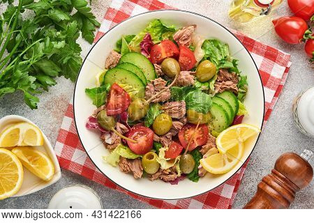 Tuna Salad With Fresh Vegetables, Olives, Capers And Lemon Served In Bowl On Light Grey Background.