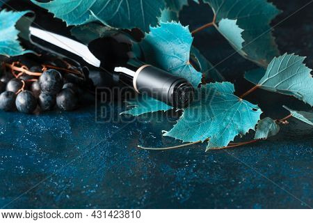 Unopened Red Wine Bottle, Vine Twig, And Ripe Grapes On An Old Blue Table. Copy Space.