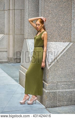 Woman Relaxing Outside. Dressing In A Green Maxi Tank Dress, High Heels, A Hand Resting On Her Head,