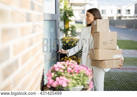 Young Woman Carrying Parcels Home, Standing With A Heap Of Cardboard Boxes On The Porch Of Her House