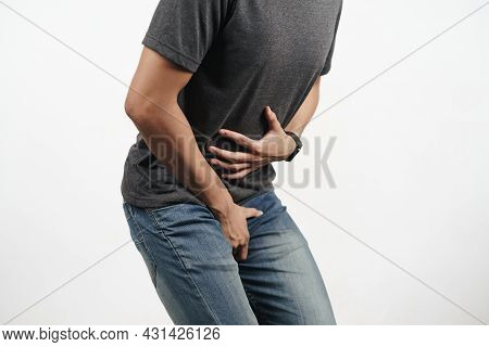 Young Man Holding His Stomach And Crotch Suffering From Diarrhea, Incontinence, Prostatitis, Venerea