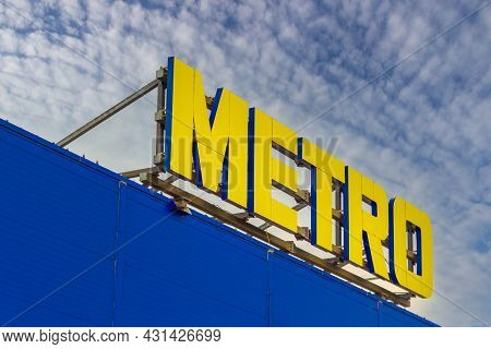 Krasnoyarsk, Russia - August 25, 2021: Emblem Of The Metro On Facade Of A Supermarket Against The Bl