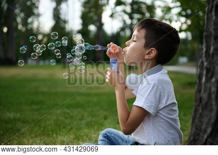 Adorable Handsome Preadolescent Boy Blowing Starting Soap Bubbles On The Park, Resting During His Sc