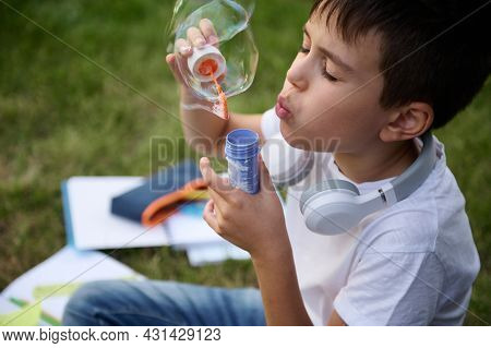 Headshot Of An Elementary Aged Schoolboy Resting In The Park Sitting On The Green Grass After School