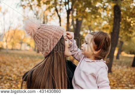 Ways To Carry A Toddler. Close Up Outdoors Portrait Of Happy Family Mom And Toddler Baby Girl In Fal
